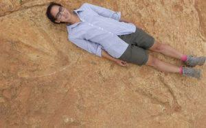 researcher lying next to dinosaur tracks